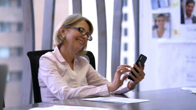 Mature business woman sitting at the office chatting on smartphone smiling