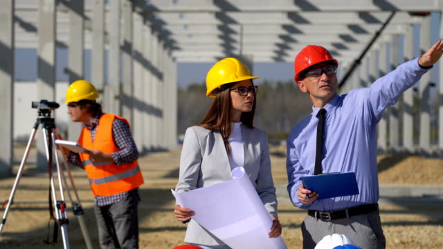Mature Businessman and Young Female Architect Planning Construction Project at Construction Site