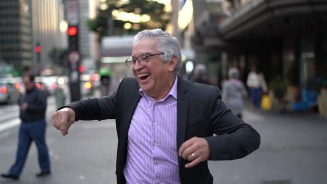 mature businessman dancing and having fun at street - solo un uomo video stock e b–roll
