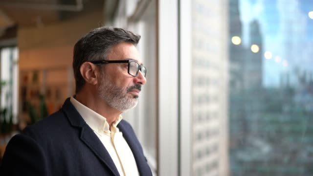 Mature businessman looking out of window Mature businessman looking out of window business goals stock videos & royalty-free footage
