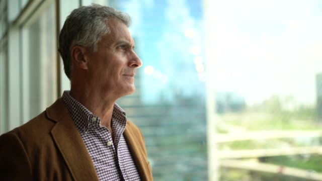 mature businessman looking out of window - uomo nostalgia video stock e b–roll
