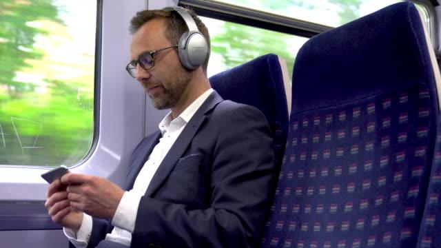 成熟的商人在火車上戴著無線耳機流線上內容到手機 - 休閒器具 個影片檔及 b 捲影像