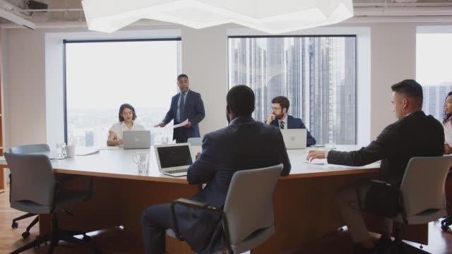 vídeos de stock e filmes b-roll de mature businessman standing giving presentation to colleagues sitting around table in modern officeê - chair