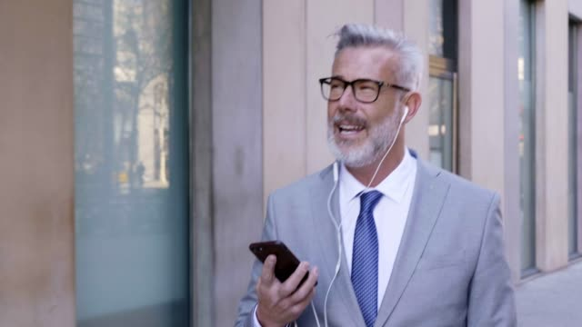mature businessman talking on mobile phone in city - capelli grigi video stock e b–roll