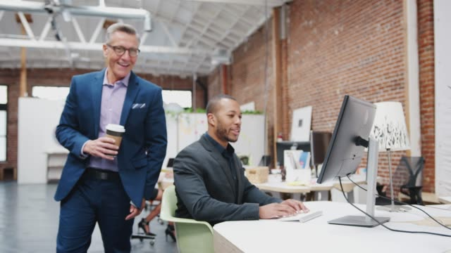 mature businessman talking to colleagues as they work at desks in modern open plan office - continente americano video stock e b–roll