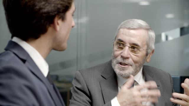 stockvideo's en b-roll-footage met rijpe zakenman die aan jongere collega spreekt - omgeving