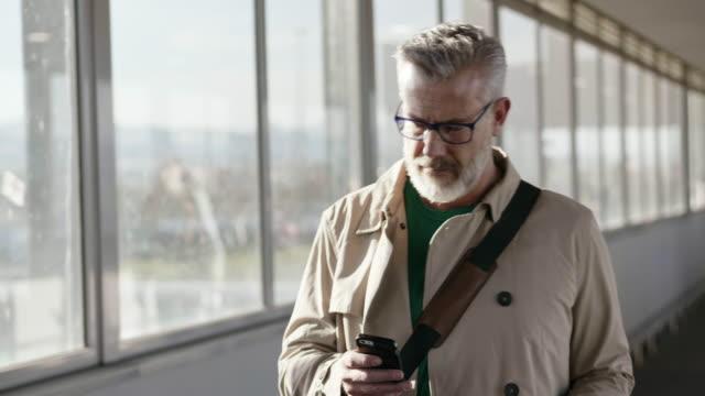 olgun işadamı havaalanında cep telefonu kullanıyor - orta yaşlı adam stok videoları ve detay görüntü çekimi