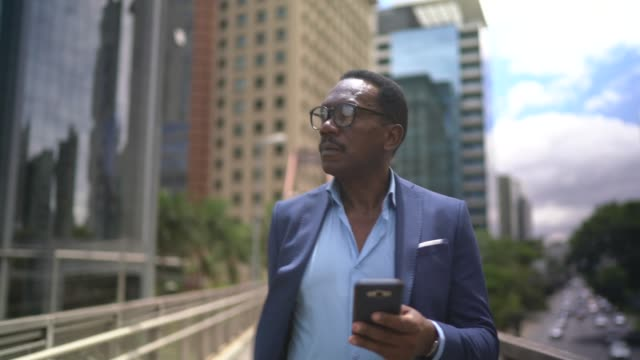 Mature businessman walking and using mobile phone at city