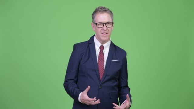 Homem de negócios maduro com os eyeglasses que explicam algo - vídeo