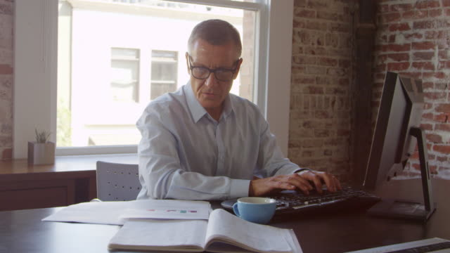 Mature Businessman Working On Computer In Office Shot On R3D video