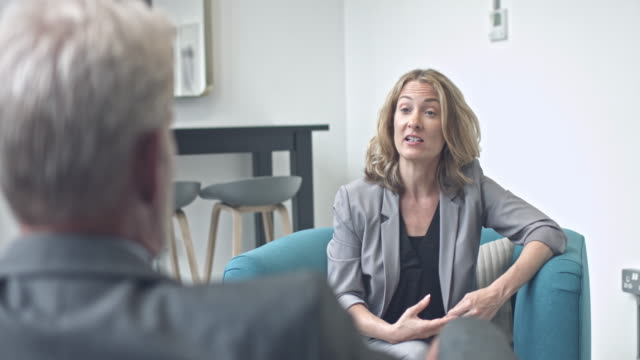 Mature businesswoman discussing with colleague in modern office video