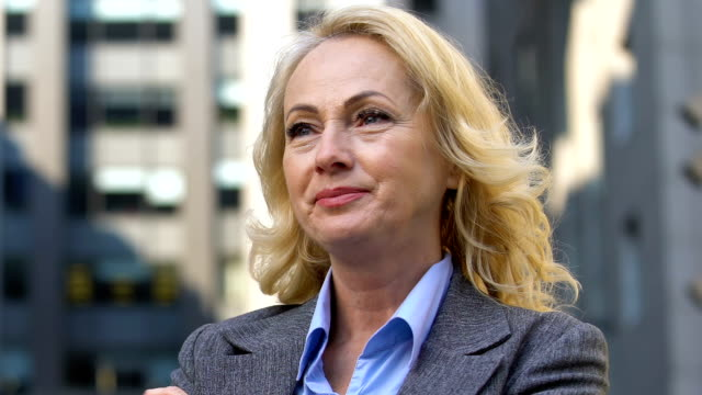 Mature businesswoman looking afar, confident in victory, successful career