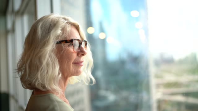 Video Mature businesswoman looking out of window
