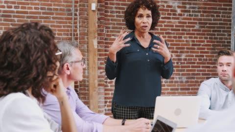vídeos y material grabado en eventos de stock de madura empresaria de pie y líder reunión de la oficina alrededor de la mesa - liderazgo