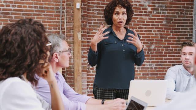 vídeos de stock e filmes b-roll de mature businesswoman standing and leading office meeting around table - liderança