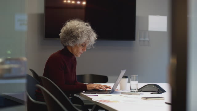 Mature Businesswoman Working Late In Office Meeting Room Using Laptop Mature businesswoman working late in office meeting room using laptop - shot in slow motion ceo stock videos & royalty-free footage