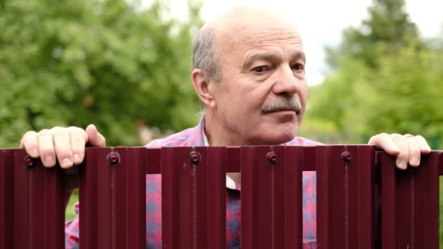 Mature caucasian man carefully watching over the fence. Curious neighbors and private life