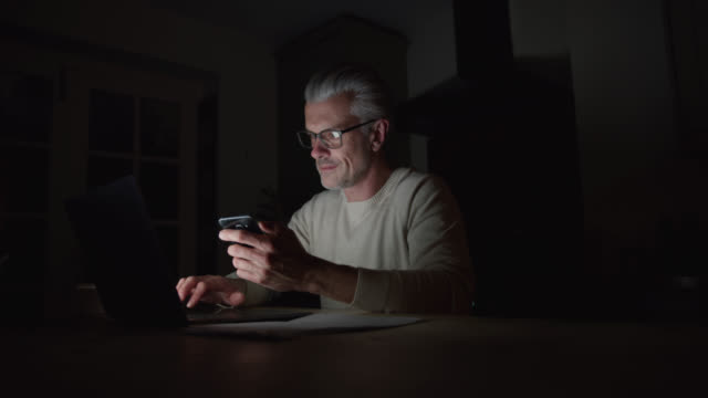 Mature caucasian man working late at home using smartphone and laptop