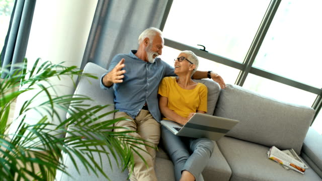 mature couple browsing through social mnetworks networks. - capelli grigi video stock e b–roll