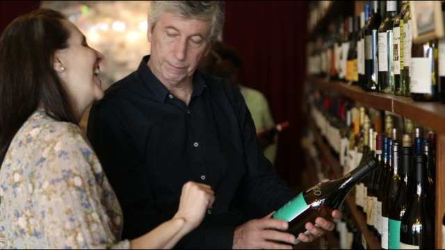 Mature couple buying wine at winery store
