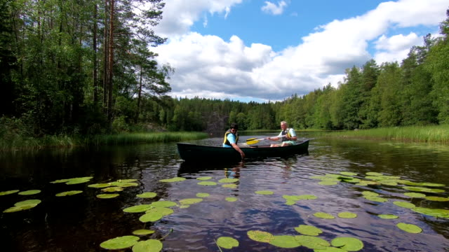 mature couple canoeing on a forest lake in finland. - fedeltà video stock e b–roll