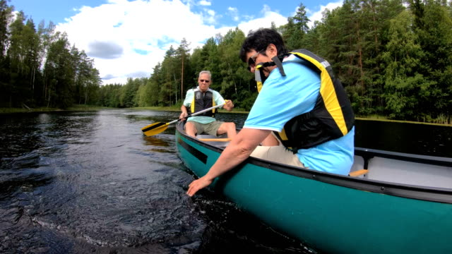 Mature couple canoeing on a forest lake in Finland.