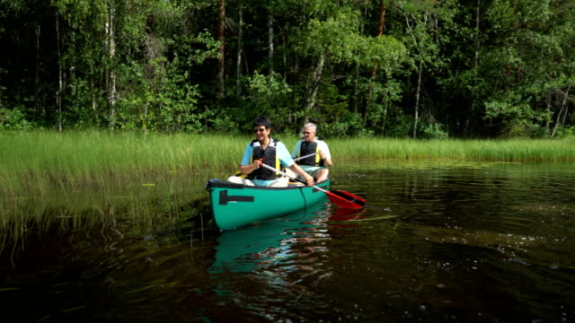 mature couple canoeing on a forest lake in finland. - ekoturystyka filmów i materiałów b-roll