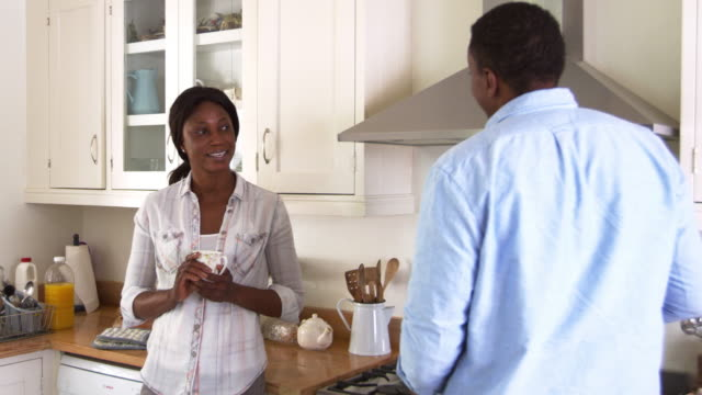 Mature Couple Chat In Kitchen As Man Prepares Meal In Kitchen video