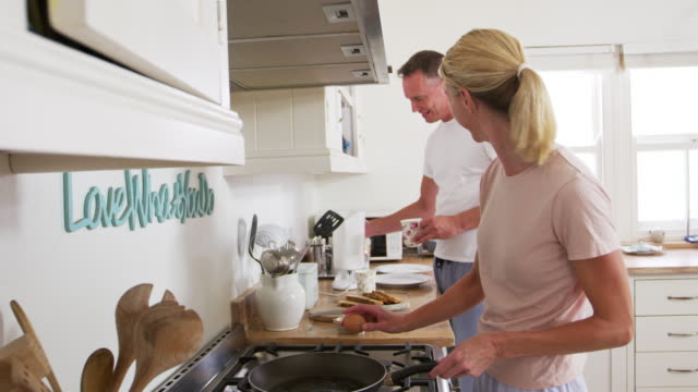 Mature Couple Chat In Kitchen As Woman Prepares Breakfast video