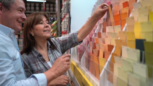 vidéos et rushes de couples mûrs choisissant des échantillons de couleur à un magasin d'amélioration de l'habitat parlant - hlm