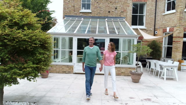 mature couple coming out of conservatory and walking across lawn holding hands - london architecture stock videos & royalty-free footage