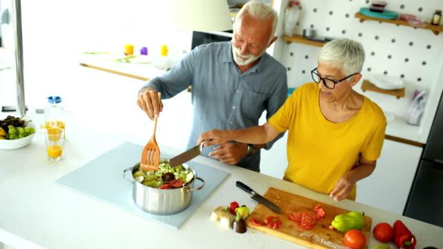 vídeos de stock e filmes b-roll de mature couple cooking lunch together. - cooker happy