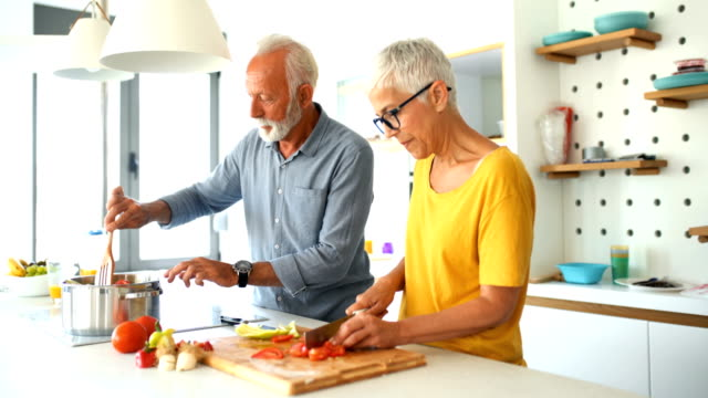 Mature couple cooking lunch together. Closeup side view of a mid 60's couple having fun while preparing lunch in a brightly lit white colored kitchen. Bearded gentleman is stirring the soup while the lady is chopping vegetables. short hair stock videos & royalty-free footage