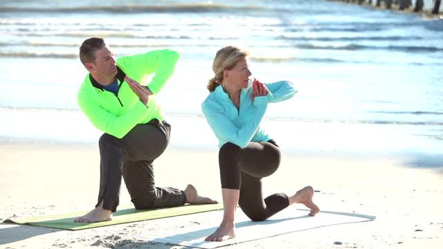 älteres paar yoga-übungen am strand - in den vierzigern stock-videos und b-roll-filmmaterial