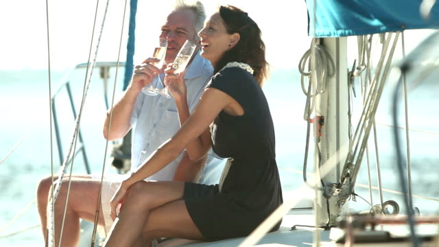 Mature couple drinking champagne on deck of sailboat video