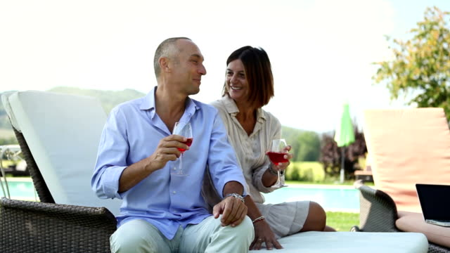 Mature couple drinking wine and relaxing video