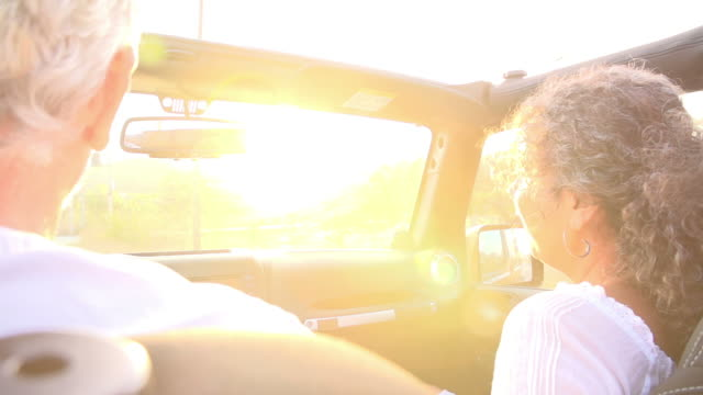 Mature Couple Driving Along Country Road In Open Top Car video