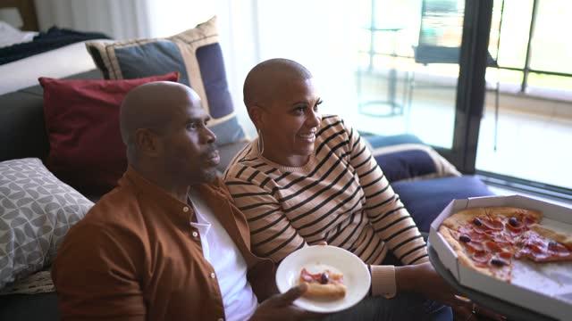 olgun çift pizza yiyor ve evde televizyon izliyor - ultra yüksek çözünürlüklü televizon stok videoları ve detay görüntü çekimi