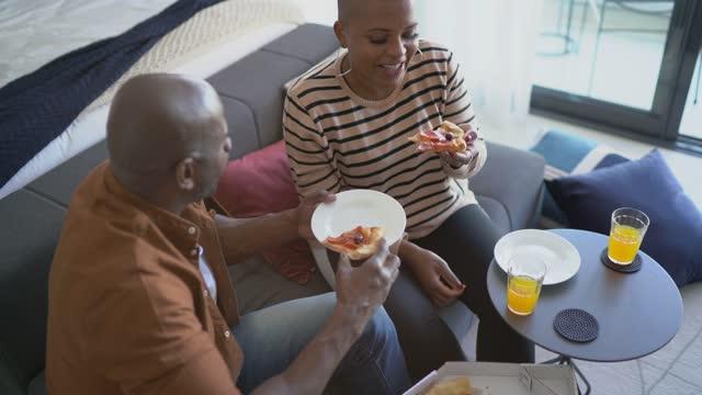 coppia matura che mangia pizza a casa - flirtare video stock e b–roll