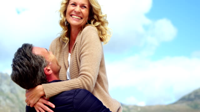 mature couple enjoying on beach - bello video stock e b–roll