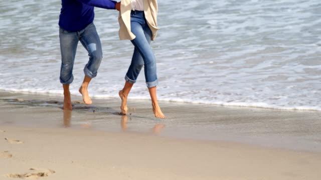 mature couple enjoying on beach - quarantenne video stock e b–roll