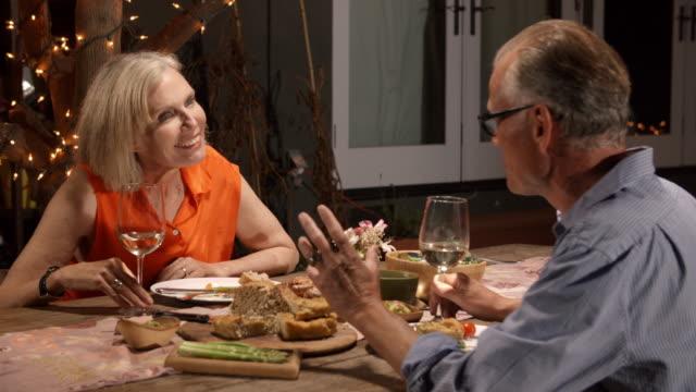 vídeos y material grabado en eventos de stock de madura pareja disfrutando de una comida al aire libre en el patio trasero - toma mediana