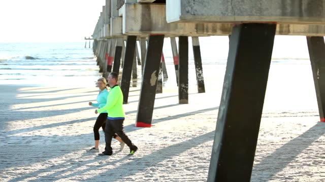 Mature couple exercising, walking on beach