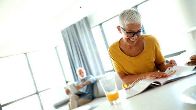 Mature couple having a morning coffee at a kitchen counter. Closeup of a cheerful mid 60's couple having a morning coffee on a weekend morning. She's having orange juice and reading a magazine, from time to time turning around to her her husband who's reading his daily newspapers on sofa in the background. short hair stock videos & royalty-free footage