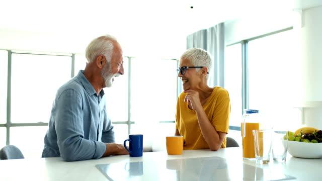 vídeos y material grabado en eventos de stock de pareja madura tomando un café de la mañana en un mostrador de la cocina. - cabello corto
