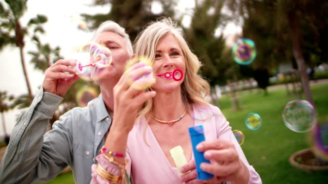 mature couple having fun blowing bubbles at the park - coppia anziana video stock e b–roll