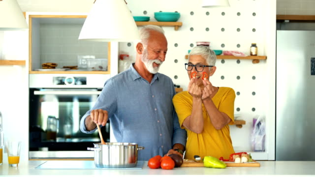 vídeos de stock e filmes b-roll de mature couple having while cooking lunch. - cooker happy