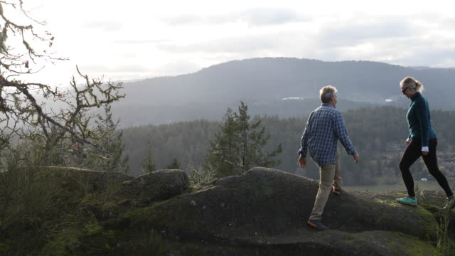 Mature couple hike along mossy rock spine