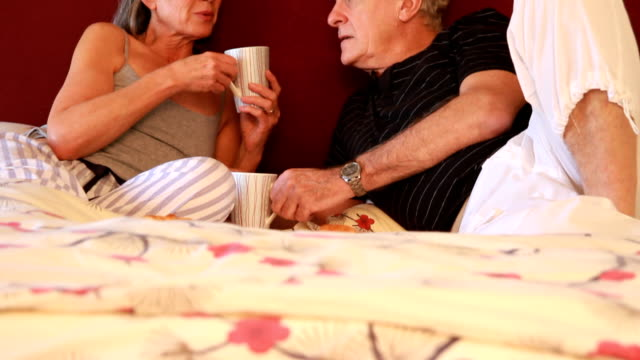Mature couple in bed talking and drinking coffee video