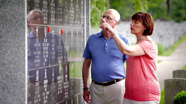 Mature couple in Veterans memorial A mature couple read the names of the brave Veterans on a memorial. memorial day stock videos & royalty-free footage